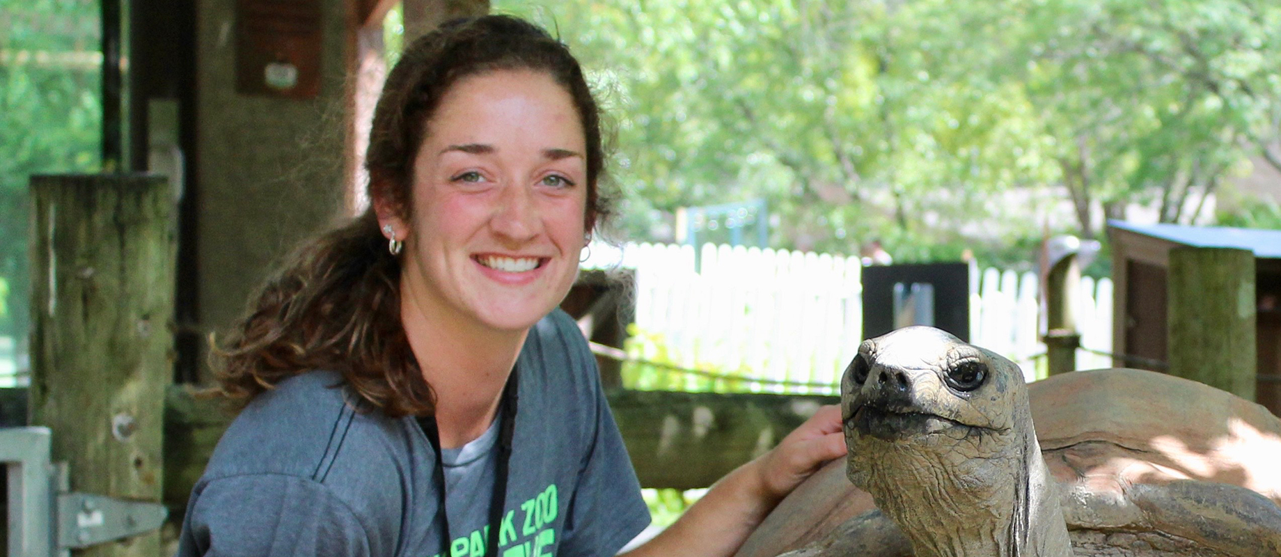 Simpson College graduate Emma Fleddermann with a tortoise at Blank Park Zoo.