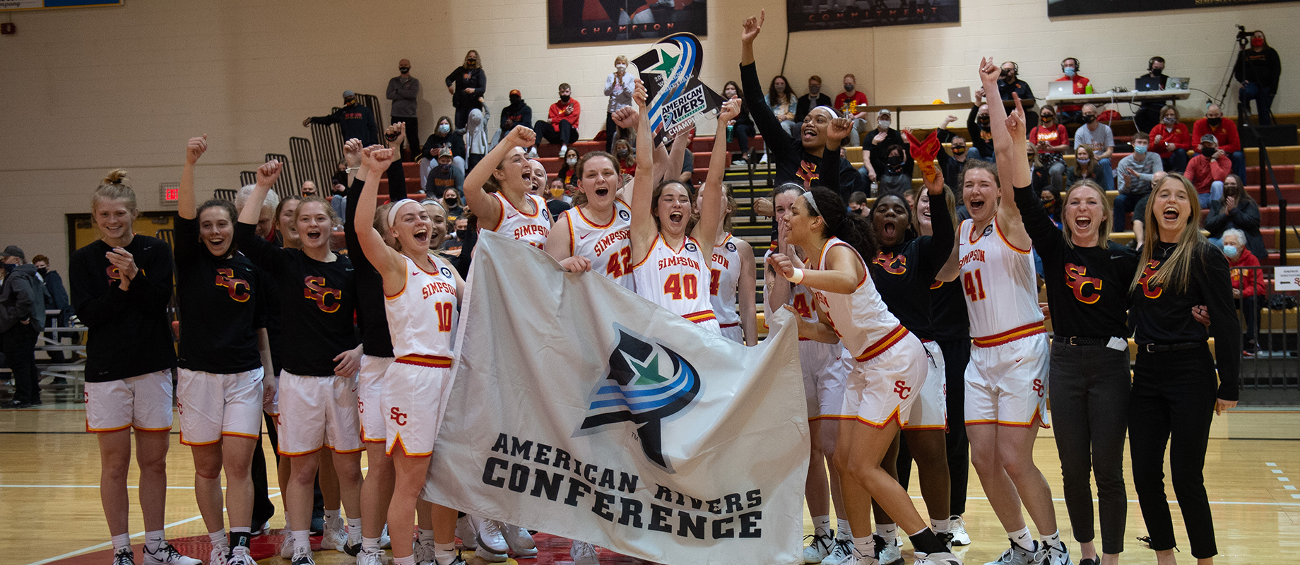 The Simpson College women's basketball team poses with the American Rivers Conference trophy.