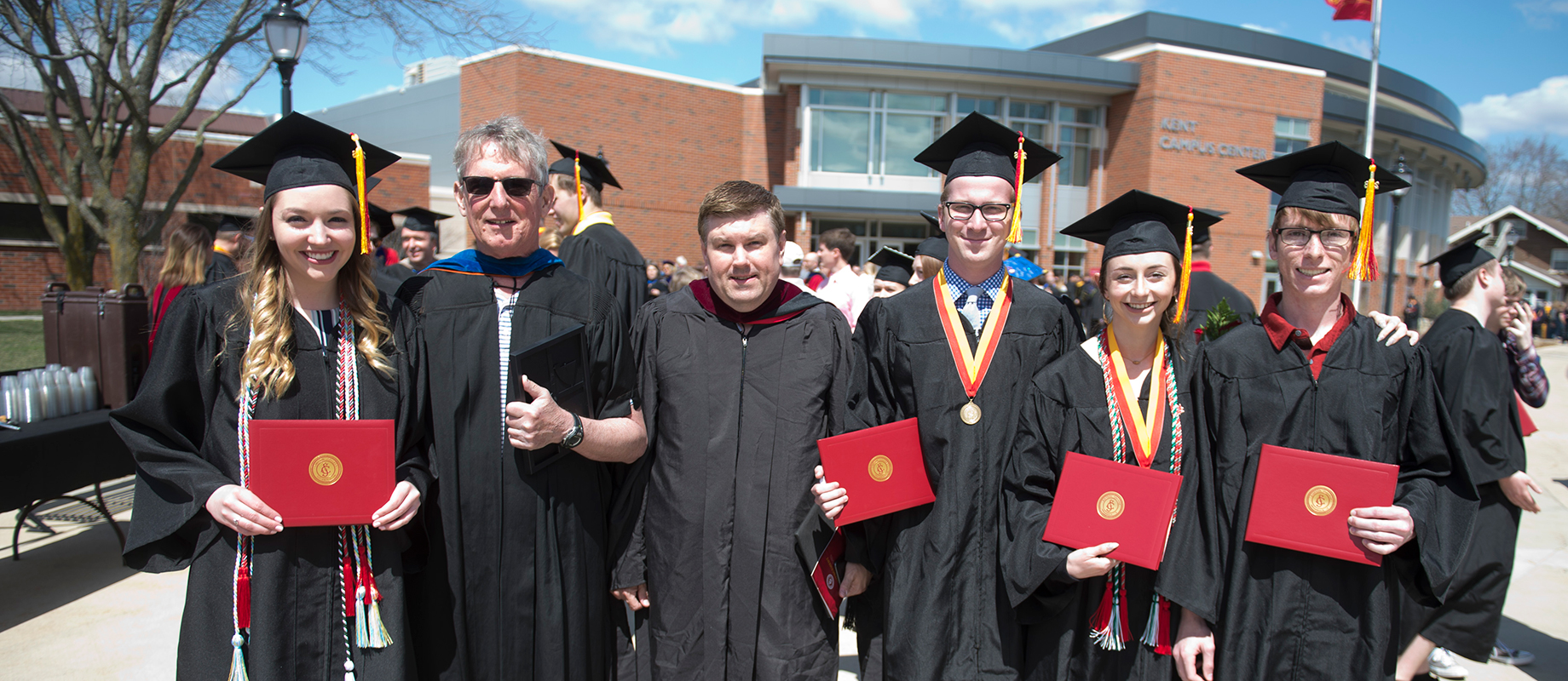 Marty Feeney poses with students at commencement.